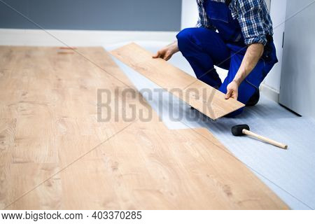 Worker Installing Home Floor. Carpenter Laying Laminate Flooring