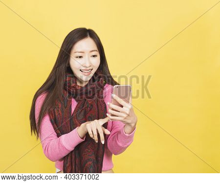 Happy Young Woman Looking And Holding Mobile Phone