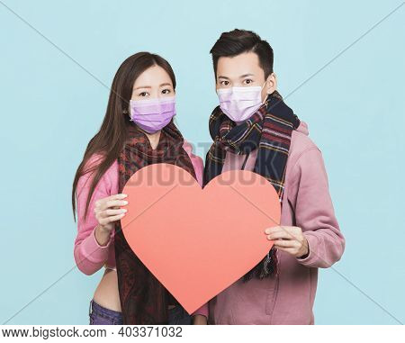 Young Couple Wearing  Protective Face Mask And Showing Red Heart Symbol