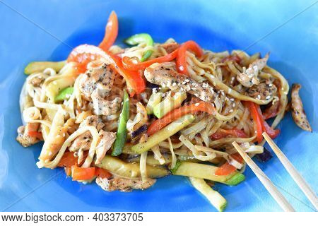 Udon With Chicken And Vegetables In Soy Sauce On Blue Plate. For Asian Food Menu