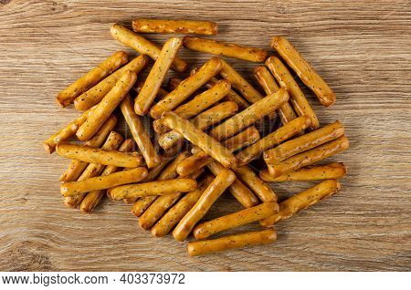 Heap Of Breadsticks With Poppy On Brown Wooden Table. Top View