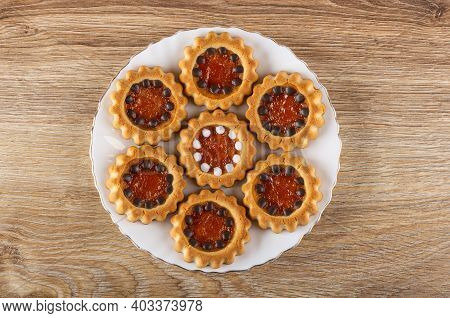 Cookies With Filling From Orange Jam And Chocolate In Glass Plate On Wooden Table. Top View