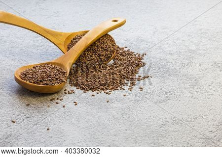 Flax Seeds In A Wooden Spoon On A Concrete Background, A Dietary Product That Reduces Cholesterol, A