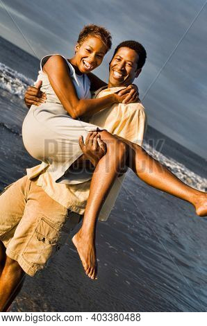 Photo of cheerful young African American man carrying woman on beach