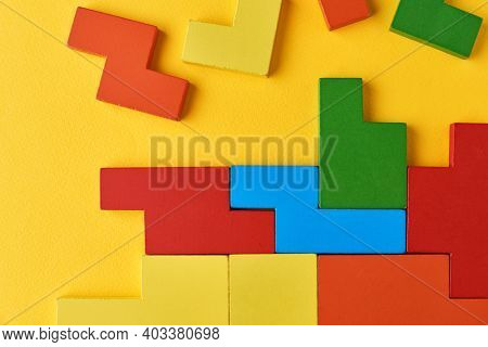 Different Wooden Blocks On Yellow Background. Concept Of Logical Thinking And Education