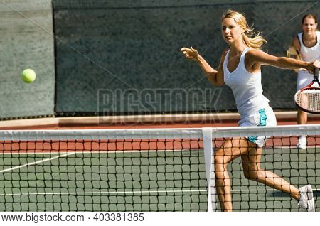 Portrait of young attractive tennis woman player hitting the ball