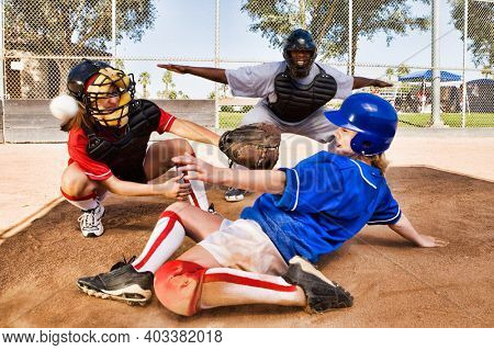Portrait of Softball player sliding into home plate while umpire rules safe