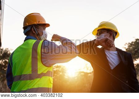 Asian Industry Construction Site Worker And Foreman Wearing Hygiene Face Mask Elbow Bump Greeting Ad