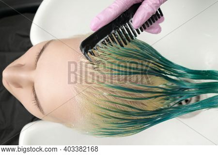 Top View Of Hairdresser Holding Wet Hair In Hand And Combing Young Woman Long Green And Discolored H