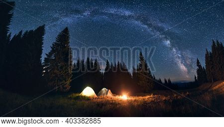 Panoramic View Of Night Camping In Valley With Large Pine Trees. Burning Campfire And Illuminated To