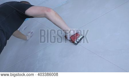 A Man In A Cheap T-shirt And Cotton Gloves With An Effort Sands A Gray Plastered Wall With A Special