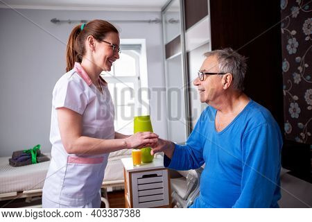 Caring Nurse Holding A Hand Of A Senior Man Occupant In A Nursing Home Room, Providing Care For The