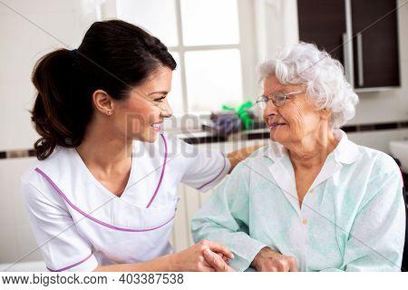 Nurse Attending Senior Woman In A Long Term Care Facility, Concept Of Trust