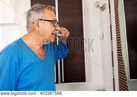 Senior Man Brushing His Teeth While Still In His Pajamas, Morning Activities Concept