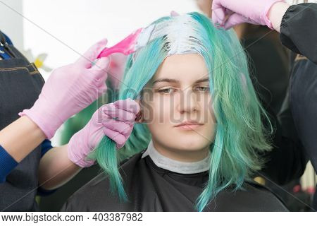 Process Of Bleaching Hair Roots In Hair Salon. Two Hairdressers In Protective Glove Use Pink Brush W