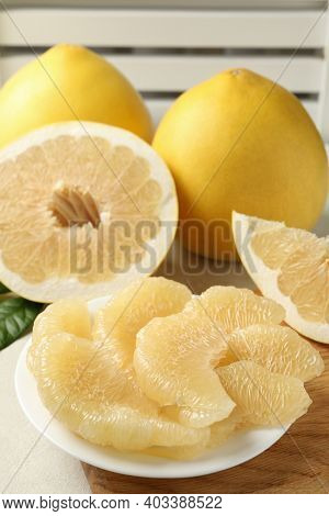 Ripe Pomelo And Plate With Pomelo Slices On White Textured Table