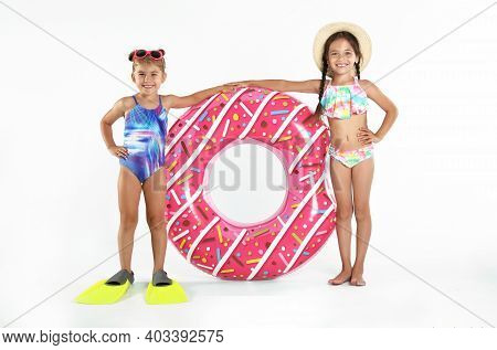 Cute Little Children In Beachwear With Bright Inflatable Ring On White Background