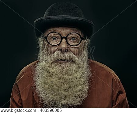 Portrait of an old-fashioned oldman with a white beard in a bowler hat and round glasses looking at the camera with big eyes. Old age. Black background.