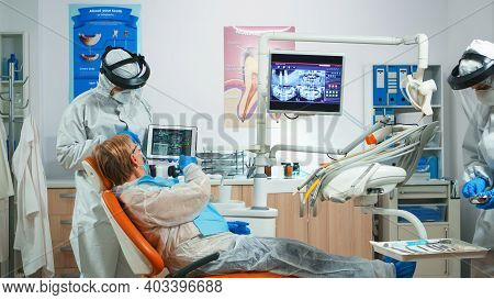 Dentist Wearing Protection Equipmentin Dental Office Examining X-ray Image On Tablet During Global P