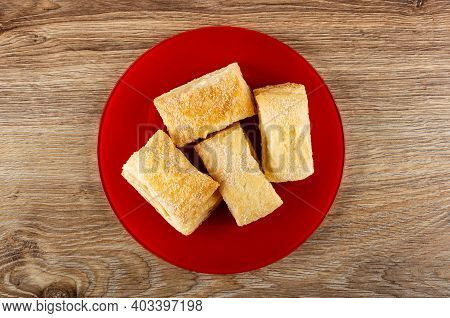 Few Puff Cookies In Red Glass Plate On Brown Wooden Table. Top View