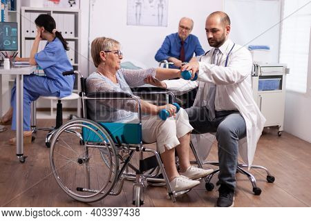 Medical Therapist Helping Disabled Senior Woman With Physiotherapy. Elderly Invalid Patients In Hosp