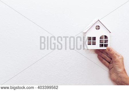 Hand Of A  Woman Holding A White Wood House Model. Real Estate Agent Offer House, Property Insurance