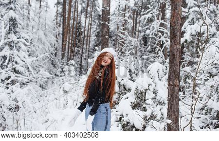 Young Red-haired Girl With Long Red Hair On A Winter Background.red-haired Woman In A White Hat On T