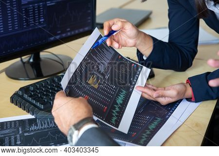Brokers Discussing Trading Strategy, Holding Papers With Financial Data, Pointing Pen At Charts. Cro
