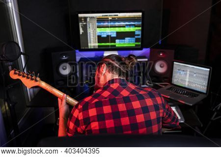 Hipster Man Playing Guitar And Sining His New Song In Stereo Studio To Record Brand-new Track . Usin
