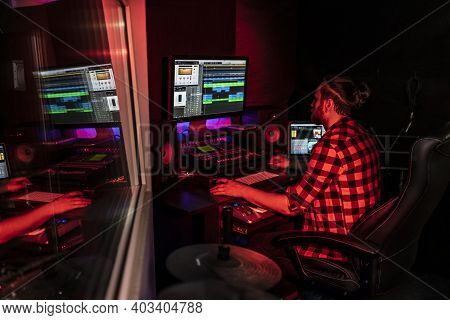 Young Producer With Beard Is Working On The Mixer With Audio And Track In The Record Studio.