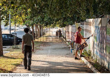 Belgrade, Serbia - August 21, 2018: Billsticker, Or Billposter Working And Sticking Advertisement Po