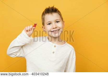 Smiling Caucasian Toddler Boy Looking To The Camera And Holding Jelly Gummy Bear In His Hand. Isolat