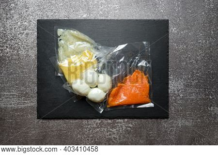 Products In Vacuum Packaging On Black Slate Board. Boiled Eggs And Vegetables For Making Salad, Vacu