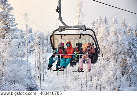 People Go Snowboarding And Skiing, Winter Recreation And Sports. Skiing Down Mountain On Snowboard,