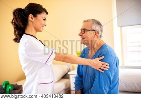 Nursing Home Doctor Providing Care To A Senior Man Resident