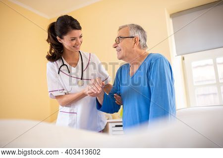 Female Doctor In A Nursing Home Facility Holding Her Patient For Hand