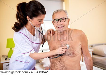 Young Brunette Doctor Using Stethoscope To Perform A Routine Check On Elder Man