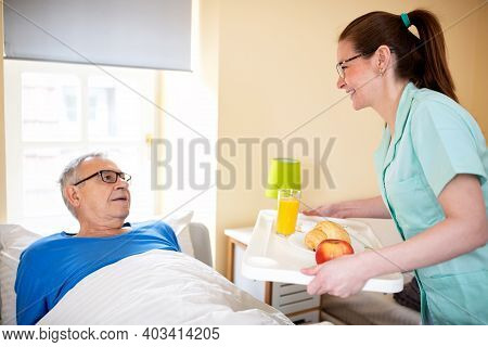 Nurse In A Old People's Home Providing Residential Care By Bringing Breakfast To Her Senior Man Occu