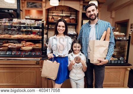 Young Happy Family Buying Bread In Modern Bakery.
