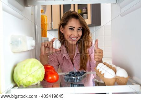 Smiling Beautiful Woman Holding An Egg Seeming Eager To Prepare Some Food With The Groceries From Th