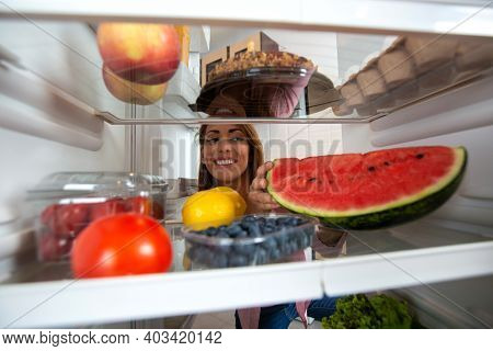 Happy Woman's Face And A Fridge Full Of Tasty And Delicious Foods
