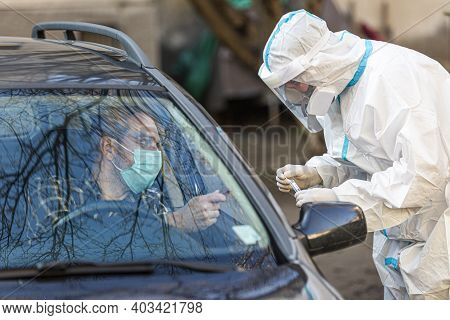 Medical Worker Performing Drive-thru Covid-19 Test, Taking Nasal Swab Sample From Male Patient Throu