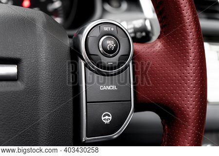 Cruise Control Buttons On The Red Perforated Leather Steering Wheel Of A Modern Car.  Car Interior D