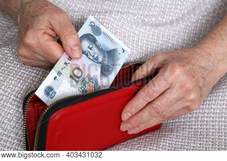 Elderly Woman Takes Out Chinese Yuan Note From Her Wallet. Concept Of Pension Payments In China, Sav