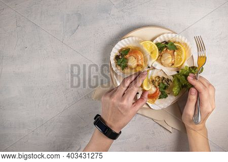 Baked Scallops With Caviar In A White Plate On A White Stone Background. Female Hands Hold Fork And
