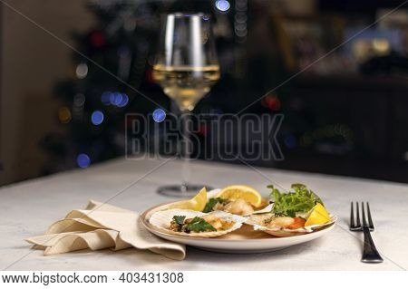 Baked Scallops With Caviar In A Plate Against The Background Of Blurred Glasses Of Wine. Scallops Wi