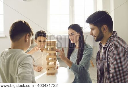 Parents And Children Playing Tumble Tower While Enjoying Quiet Activities Together