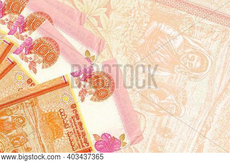 100 Sri Lankan Rupees Bills Lies In Stack On Background Of Big Semi-transparent Banknote. Abstract B