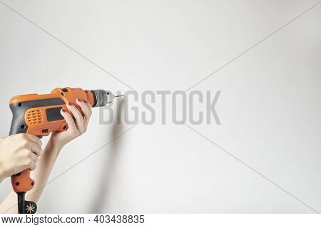 Woman With Manicured Hands Drilling A White Wall With An Orange Power Drill. Detail Image With Copy