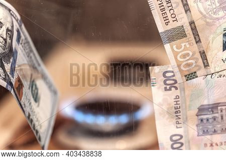Defocused Background Burning Gas From A Kitchen Gas Stove, Dollars And Ukrainian Hryvnia In The Fore